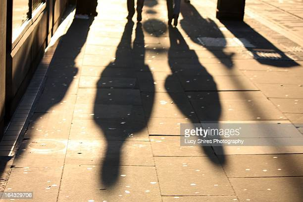 shadows of people walking on a pavement - lucy shires stock pictures, royalty-free photos & images