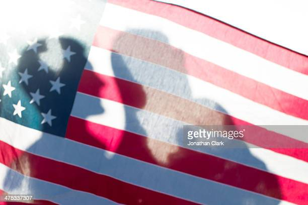 Shadows of peoples faces cast on the USA Flag