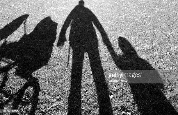 Shadows of person holding hands with a baby and a stroller