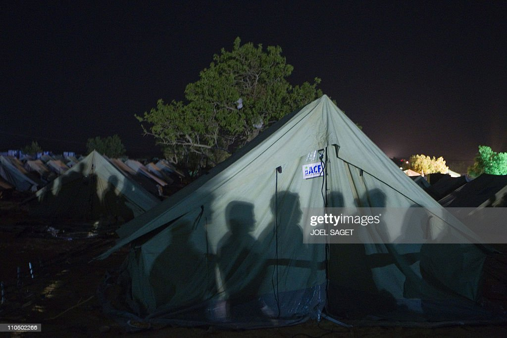 Shadows of refugees waiting for food appear on a UN tent on March 13 2011 & Shadows of refugees waiting for food app Pictures | Getty Images