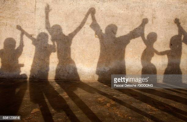 shadows of school children playing - togo stock pictures, royalty-free photos & images