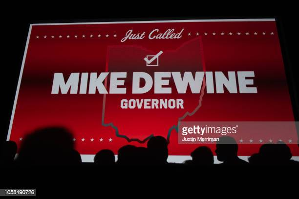 Shadows of supporters of Republican Gubernatorialelect Ohio Attorney General Mike DeWine are cast on the big screen as he takes the stage after being...