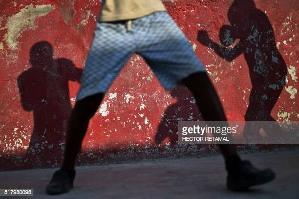 Shadows of the children while they practice shadow boxing in a courtyard in Cite Soleil PortauPrince on 22 March 2016 One of the children is Jakenson...