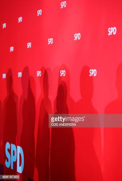 shadows of the Social Democrats Party party leadership are cast on a red wall with the SPD logo during a press conference one day after the regional...