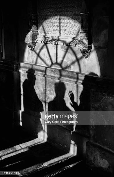 shadows of three people and arched window - gary colet stock pictures, royalty-free photos & images