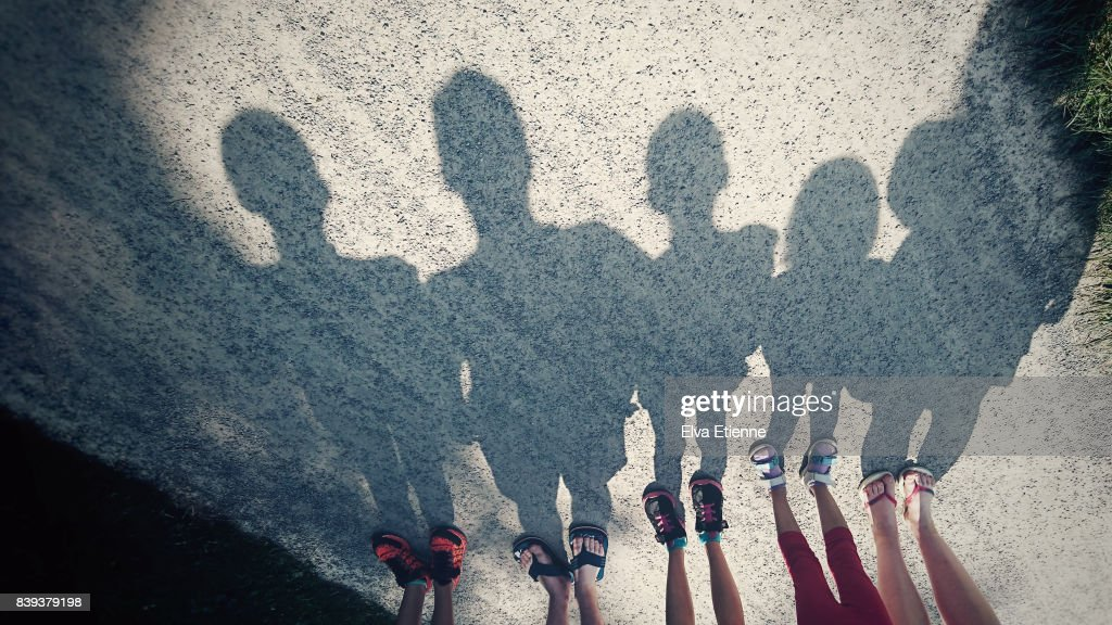 Shadows on a gravel path of a family of five : Stock Photo