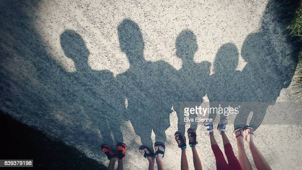 shadows on a gravel path of a family of five - schaduw stockfoto's en -beelden