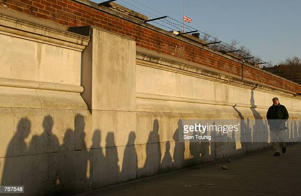 Shadows on a wall show the queue of mourners waiting to view the lying in state of the Queen Mother April 6 2002 on the Embankment in London People...