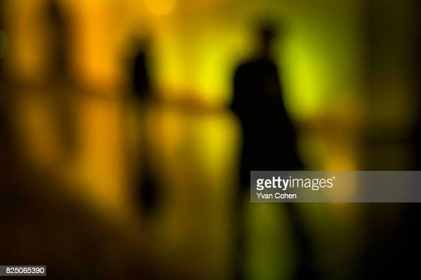 Shadowy figures walk home through the London night in the South Bank area close to Waterloo Station.
