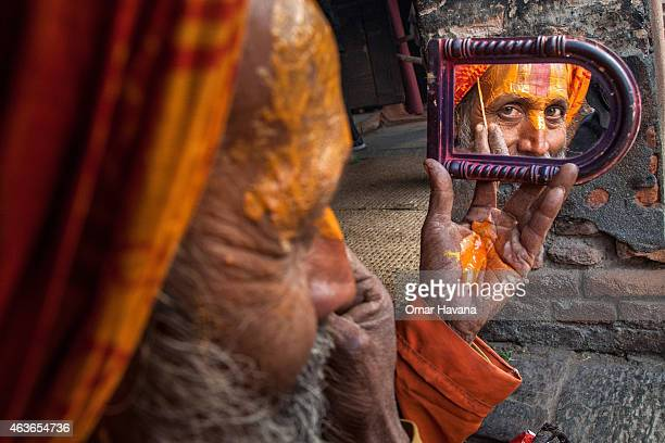 Shadu or holy man looks into a mirror while applying paint to his face inside Pashupatinath temple during the celebration of the Maha Shivaratri...