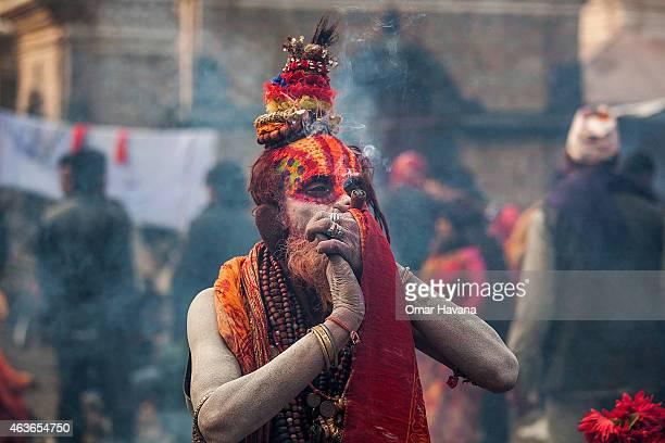 Shadu or holy man smokes cannabis with a chillum inside Pashupatinath temple during the celebration of the Maha Shivaratri festival on February 17...