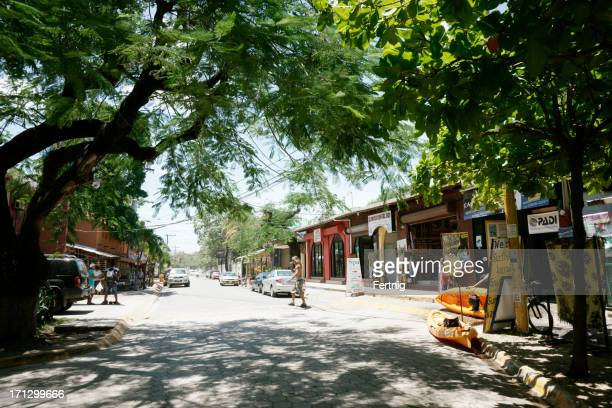 shady main street of tamarindo, costa rica. - guanacaste stock pictures, royalty-free photos & images