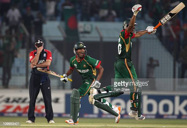 Shafiul Islam and Mahmudullah of Bangladesh celebrate scoring the winning runs as Andrew Strauss of England holds his head in his hands during the...