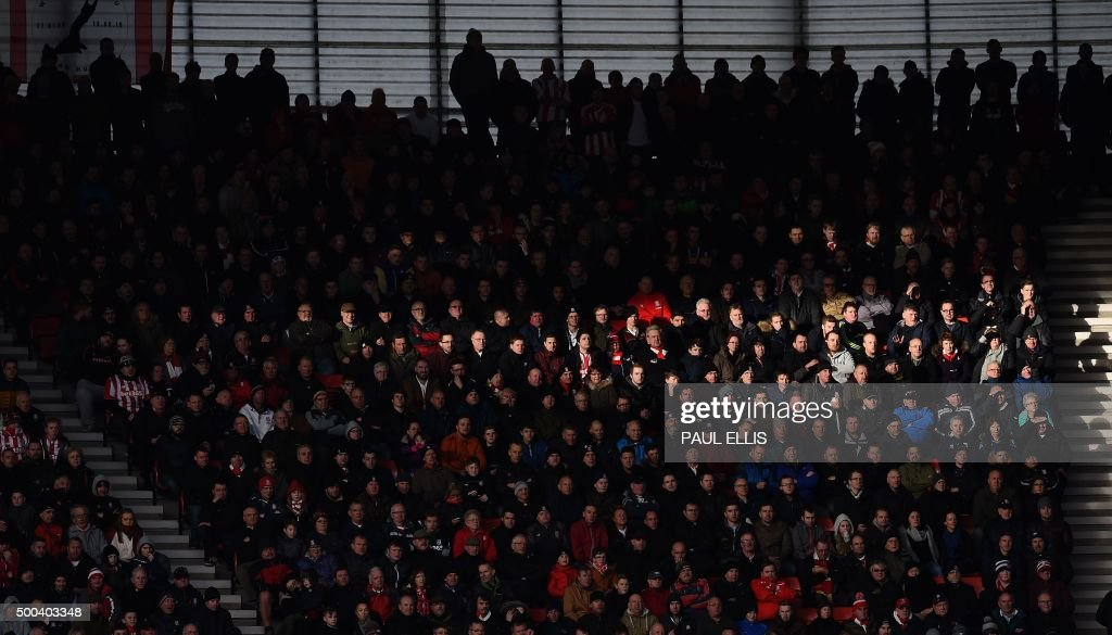 A shaft of sunlight crosses supporters during the English Premier League football match between Stoke City and Manchester City at the Britannia Stadium in Stoke-on-Trent, central England on December 5, 2015. USE. No use with unauthorized audio, video, data, fixture lists, club/league logos or 'live' services. Online in-match use limited to 75 images, no video emulation. No use in betting, games or single club/league/player publications..