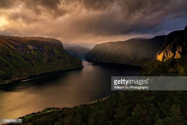 shaft of sunlight shining on the cliff of aurlandsfjord at dusk - the shining stock photos and pictures