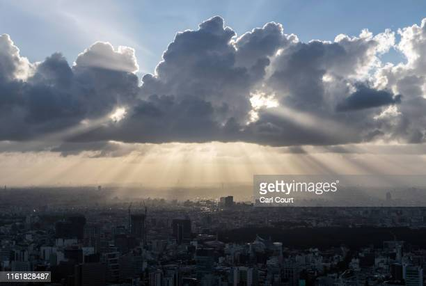 Shafts of sunlight beam down from behind clouds on August 14 2019 in Tokyo Japan