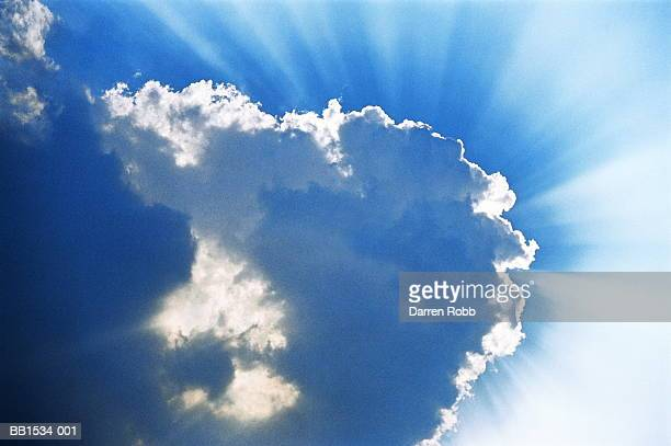 Shafts of sunlight from behind cloud in blue sky