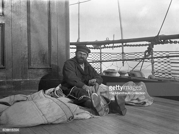 Shaggy bearded parched skin sailor in uniform wearing striped socks and hobnailed boots sitting on ships deck with canvas type sail draped across his...