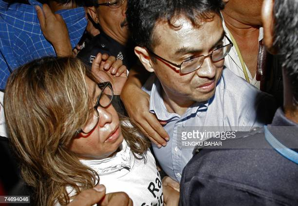 Charged Malaysian political analyst Abdul Razak Baginda is accompanied by his wife Mazlinda Makhzan as they make their way past waiting photographers...