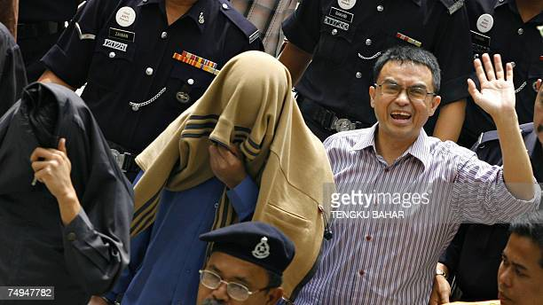 Charged political analyst Abdul Razak Baginda waves to photographers as he and charged special unit police officers Sirul Azhar Umar and Azilah Hadri...
