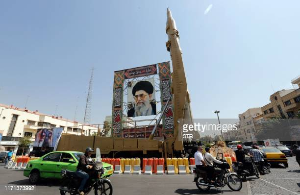 A Shahab3 surfacetosurface missile is pictured on display next to a portrait of Iranian Supreme Leader Ayatollah Ali Khamenei at a street exhibition...