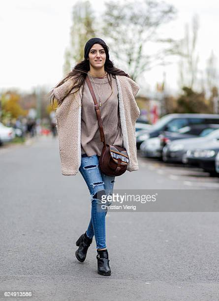 Shahar Ohayon wearing a teddy coat a brown bag blue ripped denim jeans black leggings black ankle boots black fingerless gloves black wool hat on...