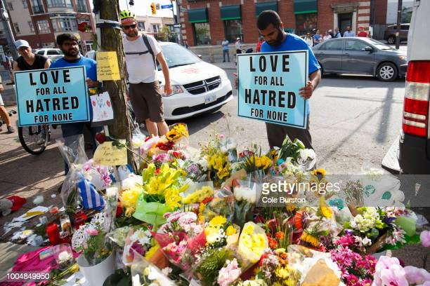 Shaheer Danial of the Ahmadiyya Muslim Community holds a sign at a makeshift memorial on Danforth Ave where people are adding flowers and messages to...