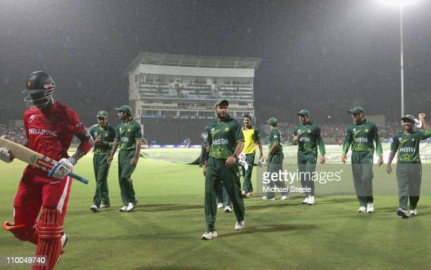 Shahid Afridi captain of Pakistan leadfs his players off the field as rain stops play for a second time during the Pakistan v Zimbabwe 2011 ICC World...