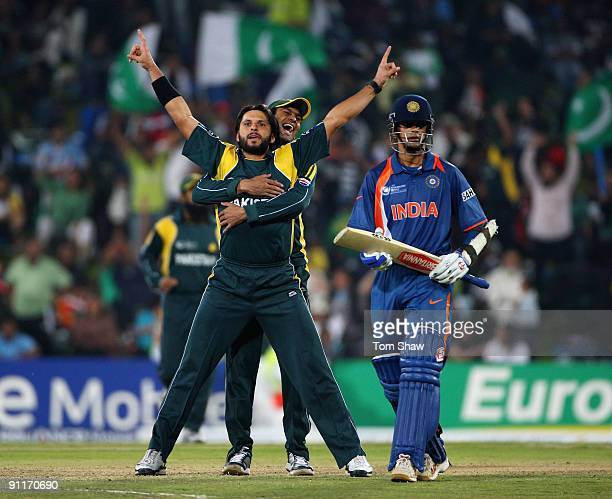 Shahid Afridi of Pakistan is hugged by his captain Younus Khan in celebration after taking the wicket of Mahendra Sigh Dhoni of India during the ICC...