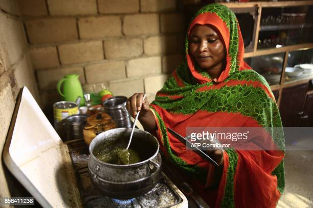 Shahinda Adel wife of Sudanese engineer Ahmed Abdallah stirs stew in a pot as she cooks in her kitchen in her home on the outskirts of the Sudanese...