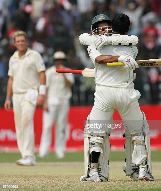 Shahriar Nafees of Bangladesh is hugged by team mate Habibul Bashar after reaching his century with Shane Warne of Australia looking on during day...