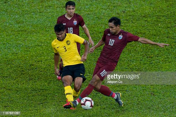 Shahrul Mohd Saad of Malaysia challenges Teerasil Dangda of Thailand during the 2022 Qatar FIFA World Cup Round Two Asian qualifier between Malaysia...