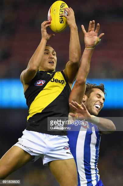 Shai Bolton of the Tigers marks over the top of Jamie Macmillan of the Kangaroos during the round 11 AFL match between the North Melbourne Kangaroos...