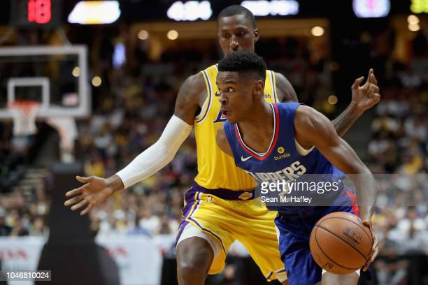 Shai GilgeousAlexander of the LA Clippers dribbles past Kentavious CaldwellPope of the Los Angeles Lakers during the first half of a NBA preseason...