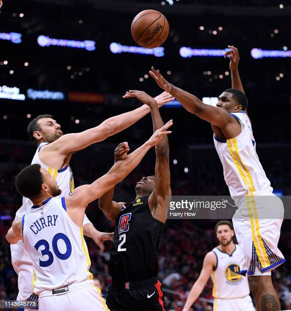 Shai GilgeousAlexander of the LA Clippers has his shot blocked by Kevon Looney Andrew Bogut and Stephen Curry of the Golden State Warriors during a...