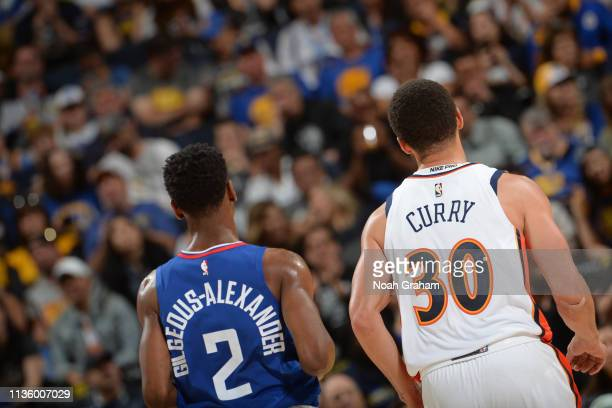 Shai GilgeousAlexander of the LA Clippers looks on with Stephen Curry of the Golden State Warriors during the game on April 7 2019 at ORACLE Arena in...