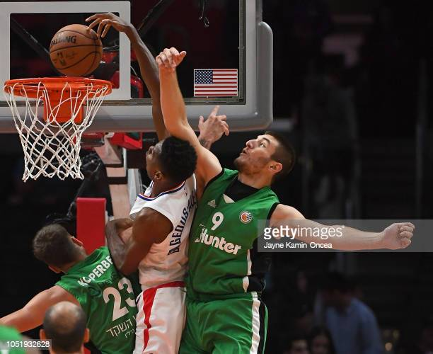 Shai Gilgeous-Alexander of the Los Angeles Clippers gets past Daniel Koperberg and Roman Sorkin of Maccabi Haifa for a dunk in the second half of the...