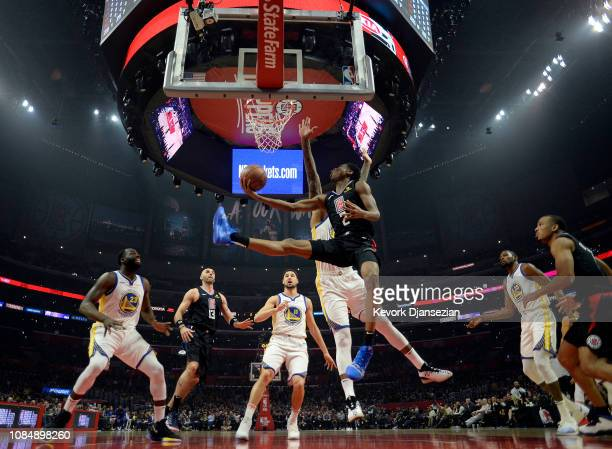 Shai Gilgeous-Alexander of the Los Angeles Clippers shoots a basket around DeMarcus Cousins of the Golden State Warriors at Staples Center on January...