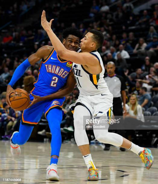Shai GilgeousAlexander of the Oklahoma City Thunder drives around Dante Exum of the Utah Jazz during a game at Vivint Smart Home Arena on December 9...