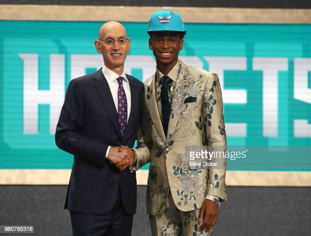 Shai GilgeousAlexander poses with NBA Commissioner Adam Silver after being drafted eleventh overall by the Charlotte Hornets during the 2018 NBA...