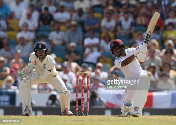 Shai Hope of West Indies plays a shot as Ben Foakes of England looks on during Day One of the First Test match between England and West Indies at...