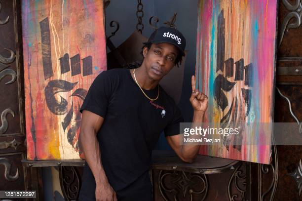 Shaka Smith poses with artwork by Amir Magal, Founder and Artist of Tribal Markers at the Ryker And Reese Host The Artists Report At TAP on June 22,...