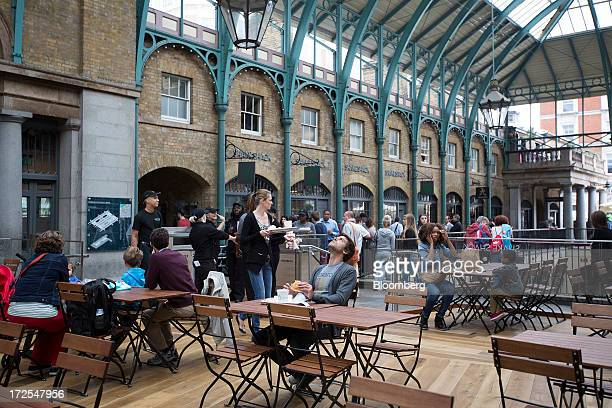 Shake Shack customers sit in a designated eating area near the company's new burger restaurant in London UK on Tuesday July 2 2013 Shake Shack...