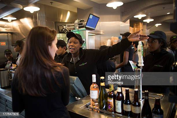 A Shake Shack employee center gestures as she speaks with a customer left at the counter inside the company's new burger restaurant in London UK on...