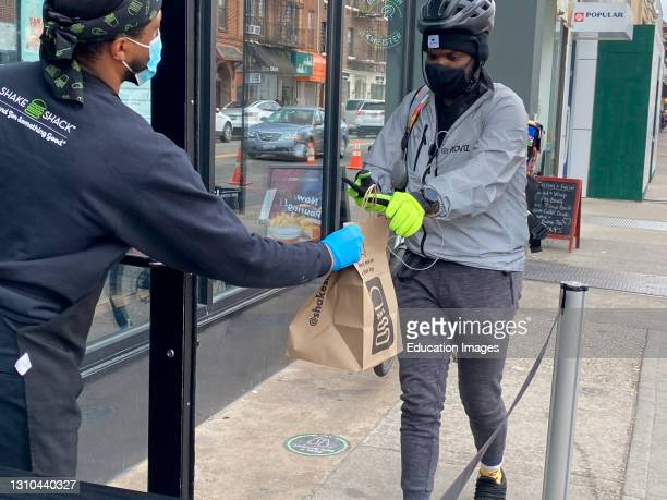 Shake Shack employee handing off food to delivery person, Queens, New York.