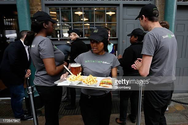 A Shake Shack employee takes a tray of food to a customer outside the company's new burger restaurant in London UK on Tuesday July 2 2013 Shake Shack...