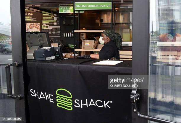 Shake Shack employee wears a masks as she prepares food orders for pickup during the Coronavirus pandemic on April 20 in Arlington, Virginia. - Shake...