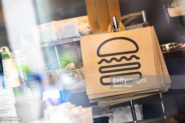 Shake Shack paper bags hang at a restaurant on April 20, 2020 in New York City. Shake Shack announced that they will return a $10 million government...