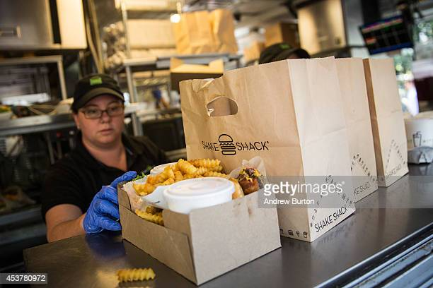 Shake Shack workers prepare orders on August 18, 2014 in Madison Square Park in New York City. Shake Shack is allegedly considering going public and...