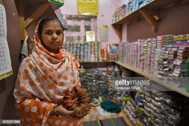 Shakeela Begum makes a living by selling bangles at her shop on March 8 2018 in New Delhi India Four months after her husbands death she took the...